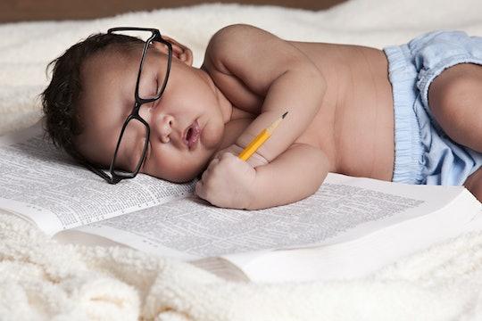 Adorable newborn sound asleep on a big book.
