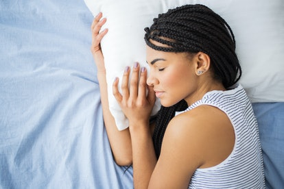 African-American teenage girl sleeping in bed