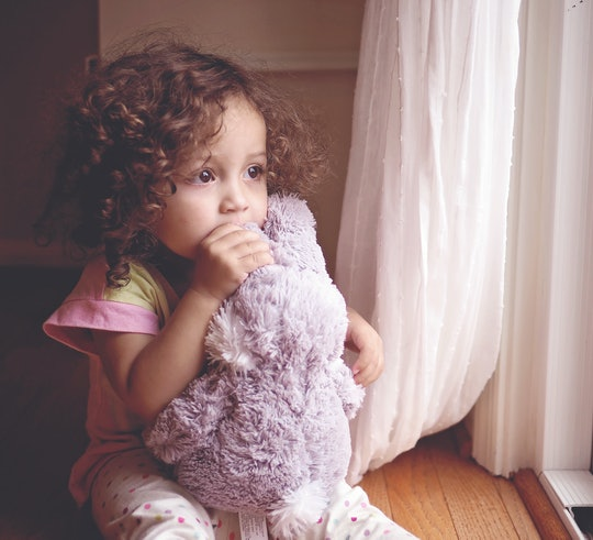 Toddler girl with curly hair sitting by a window with her stuffed animal.