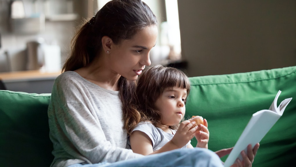 Young mother teaching daughter holding book sitting on sofa, mom or babysitter embracing little girl reading fairy tale to kid, nanny with child having fun together at home, family leisure activities