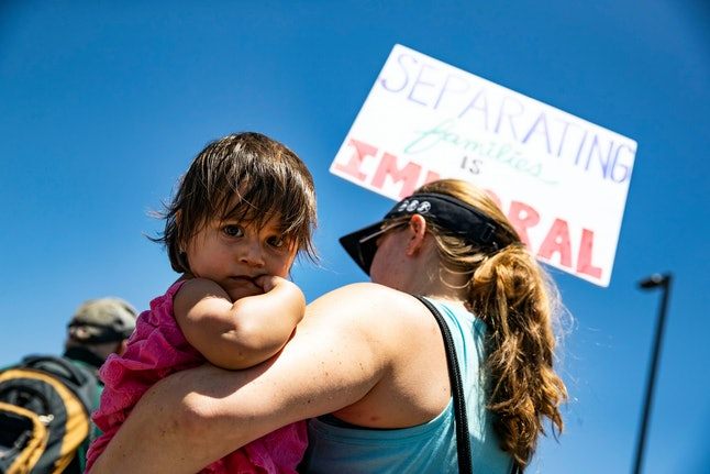 A demonstrator holds her child and a poster reading 'Separating Families is Immoral' in front of the entrance of the Otay Mesa Detention Center during a protest against migrant detention in San Diego, California, USA, 02 July 2018. This protest takes place as multiple Close the Camps demonstrations are held nation wide against migrants detention centers.