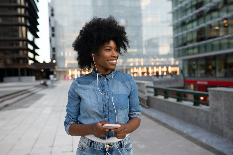 attractive happy dark skinned girl is listening to music with headphones looking at a mobile phone and smiling with a snow-white smile