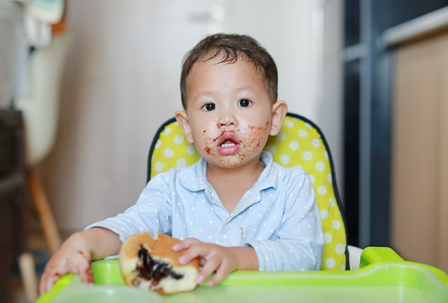 Asian little baby boy sitting on children chair indoor eating bread with Stuffed Chocolate-filled dessert and Stained around his mouth.