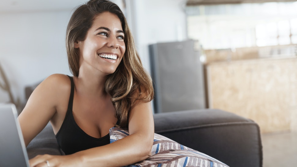 Smiling happy attractive modern businesswoman laughing joking with coworker turning around talking employee grinning delighted sitting comfortable office sofa typing laptop, researching