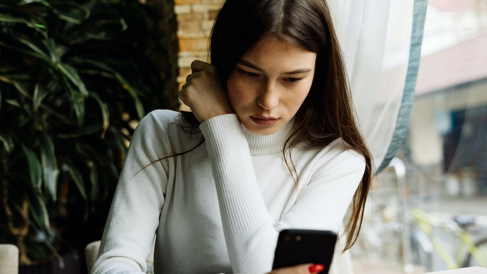 beautiful young dark-haired girl in a white sweater sits in a cafe and looks in a smartphone