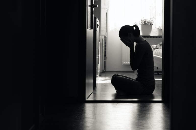 Silhouette of sad woman covering face sitting at home in a dark room.