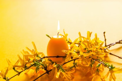 Yellow candle in the shape of egg and beautiful spring forsythia plant branches. Easter decor elements.