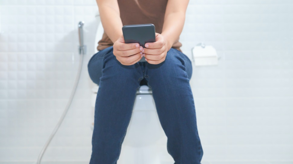 Woman sitting on toilet and using smartphone - constipation concept.