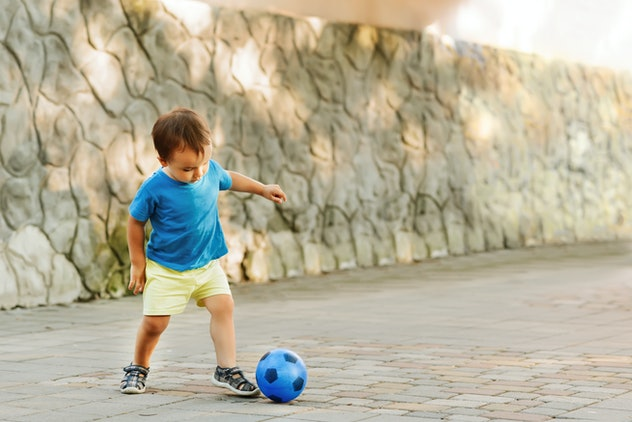 Little boy in blue shirt and yellow shorts playing football with blue tiny toy soccer ball in a sunny day in the park. Child dribbling the toy soccer ball along the paved road