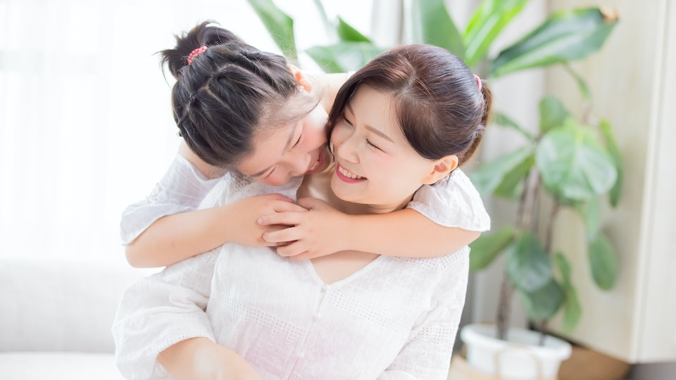 Daughter give mom a hug and mom smile happily