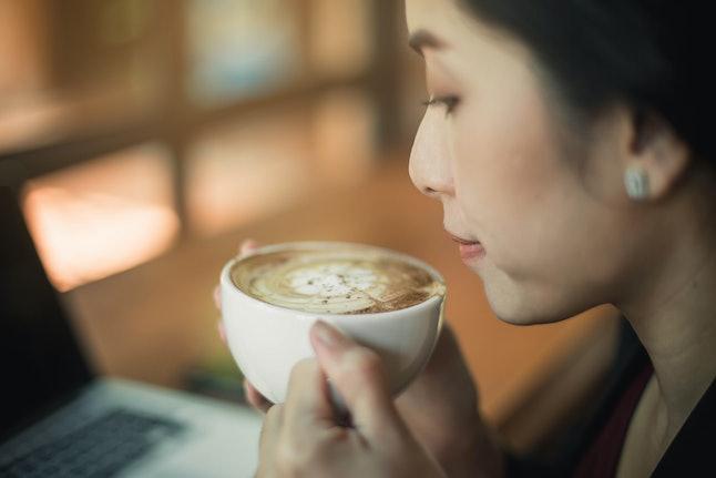 Femme buvant du café dans un café. Portrait de brunette heureux avec mug dans les mains.