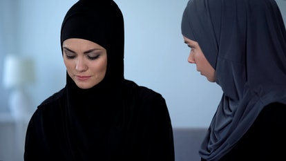 Arab woman talking with depressed friend, helping with life problems, advice