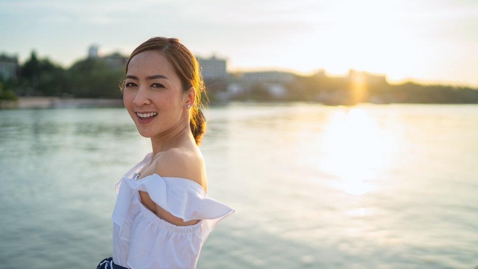 Asian beautiful girl smiling happy on sunset sea vacation enjoying warm sunshine. Mixed race Asian Caucasian pretty model outside with sun in background with white dress