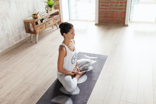Attractive young woman in a tracksuit meditating while sitting on the floor on a rug in a cozy and beautiful setting