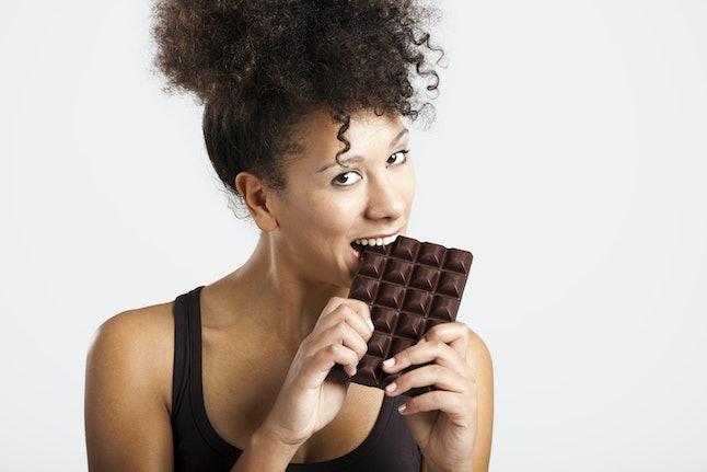 Belle femme africaine tenant et mangeant une énorme barre de chocolat noir