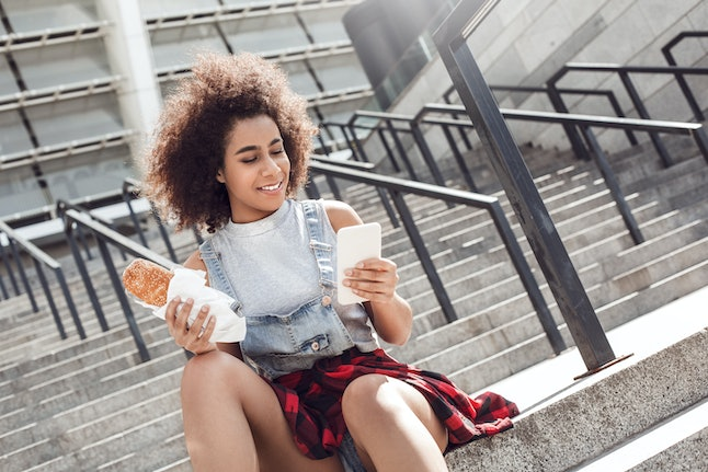 Young woman in the city street sitting on concrete stairs holding sandwich browsing internet on smartphone smiling joyful