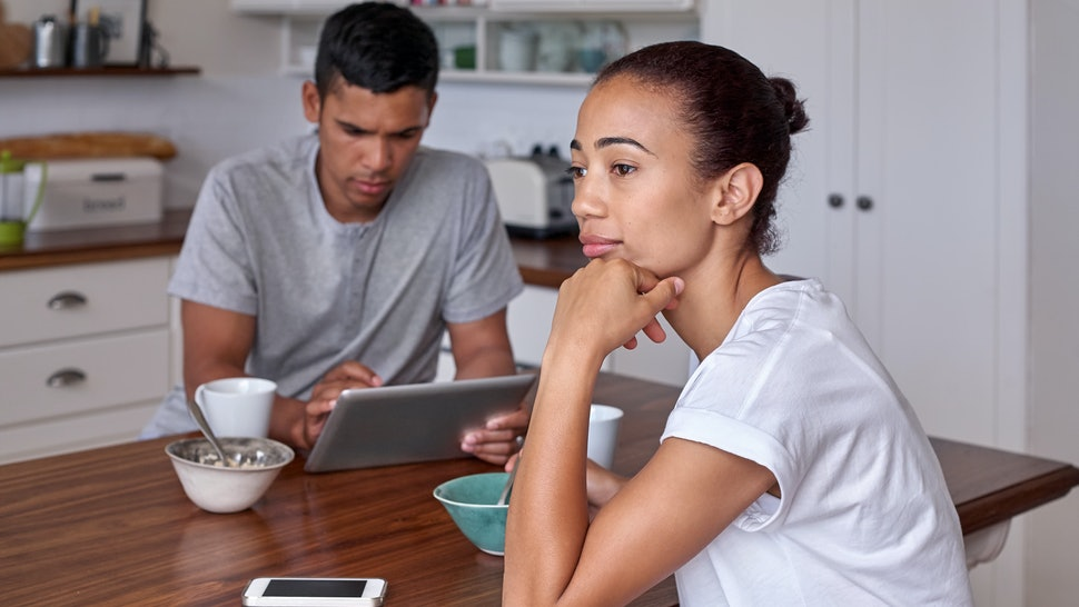 woman daydreaming over breakfast while husband is reading news on his mobile device at the kitchen counter