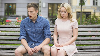 Depressed boyfriend and girlfriend sitting on bench after fight, breaking up