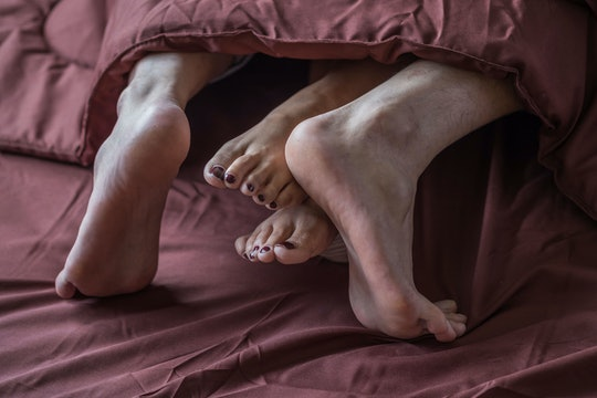 Legs of men and women are having sex on a brown bed.
