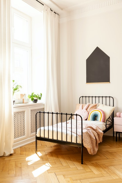 Plants on window sill in child's bedroom interior with black poster above bed with pillows. Real photo