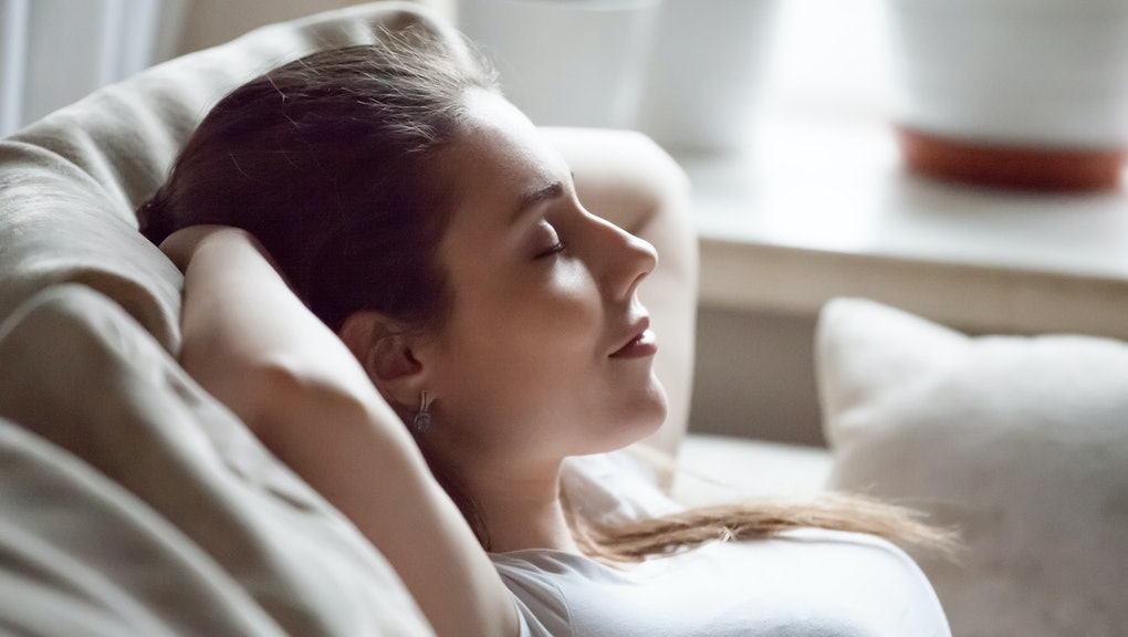 Calm pretty millennial woman lying on cozy sofa relaxing on weekend, peaceful female rest with eyes closed hands over head on couch, happy girl taking nap or chilling at home, sleep tired after work