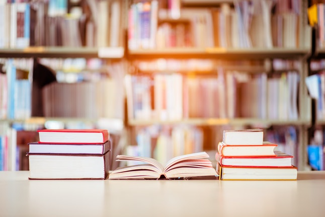 Book stack is placed on the library desk. education background, back to school concept.