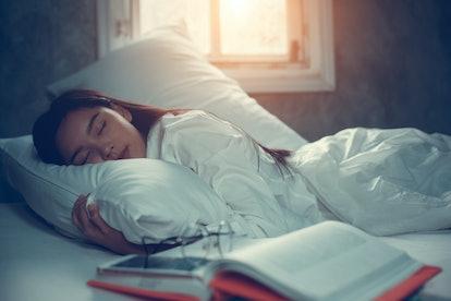 Asian teen girl lying on bed in room