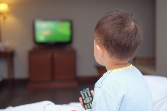 Cute little Asian 2-3 years old toddler baby boy child sitting in bed holding the tv remote control ...