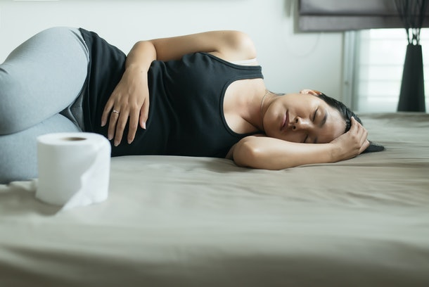 Asian woman with morning sickness and sleeping,Pregnant female nausea vomiting in bedroom,Indigestible