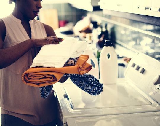 Black woman using washing machine doing the laudry
