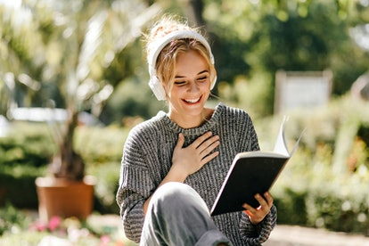 Excited beautiful girl reads her notes in warm autumn day. Outdoor photo of glad charming woman with...