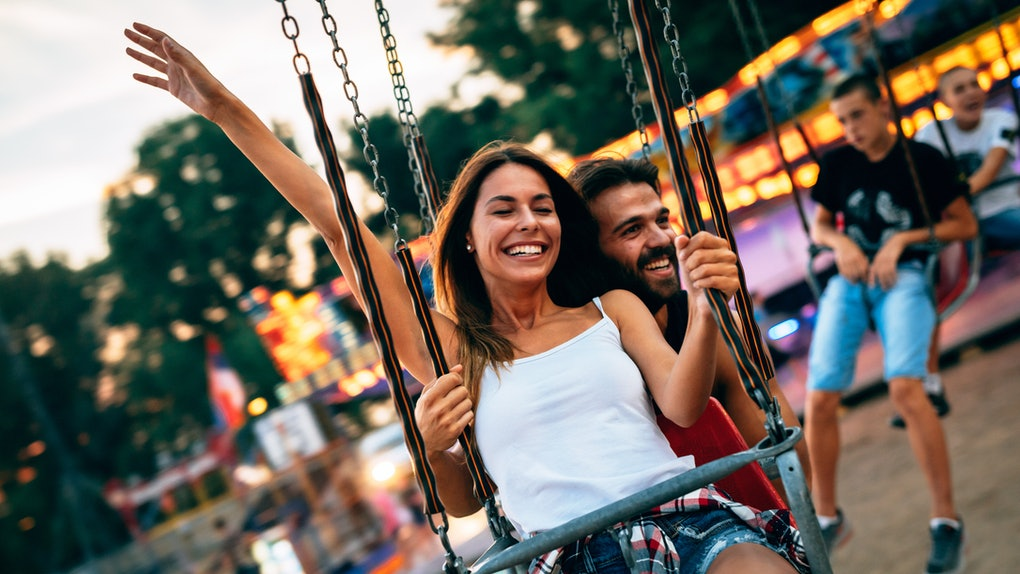 Beautiful couple having fun at amusement park. Soft focus, high ISO, grainy image.