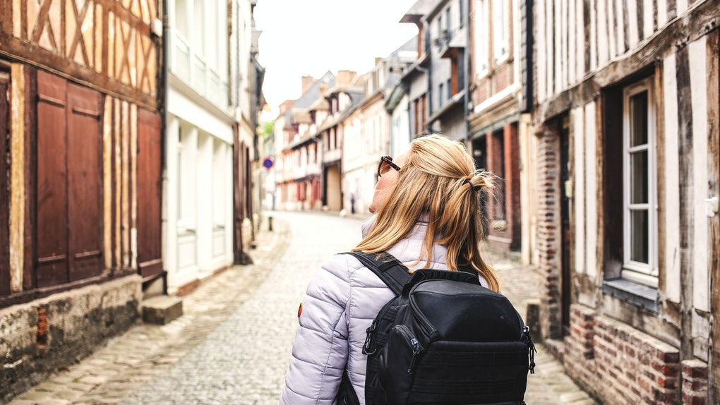 woman traveler with backpack on the streets of a quaint old town - slow travel