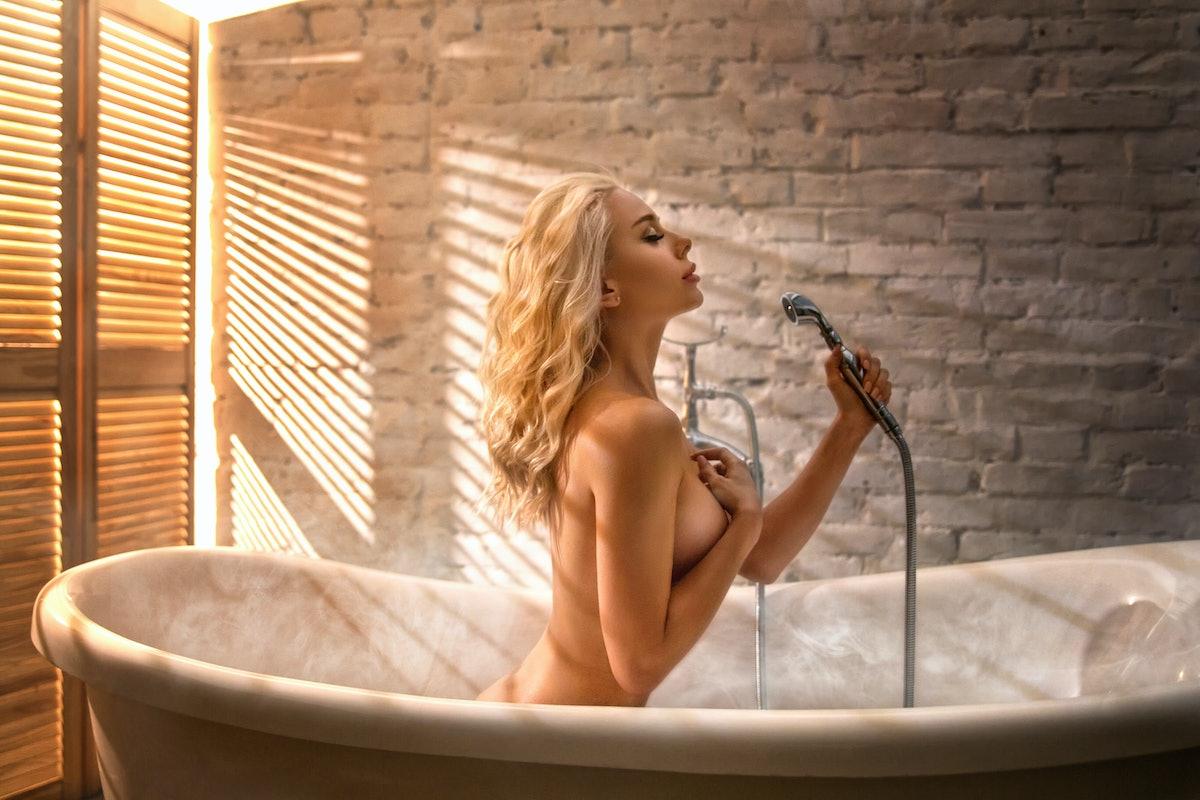Beautiful blonde woman posing in the bath with shower - beauty glamour portrait. Summer photo with l...