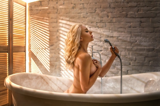 Beautiful blonde woman posing in the bath with shower - beauty glamour portrait. Summer photo with louvers light. Rejuvenation skin care therapy.