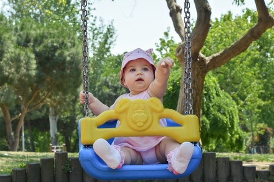 Cute adorable baby girl playing and swinging in swing in park (garden) Happy family moments concept....