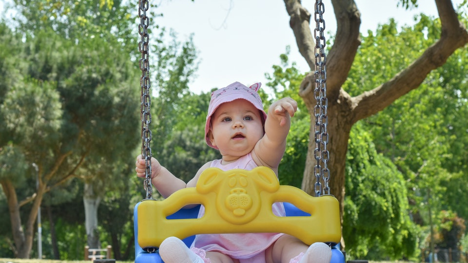 Cute adorable baby girl playing and swinging in swing in park (garden) Happy family moments concept. Family time. Outdoor activity at a playground in a summer days. Happy childhood
