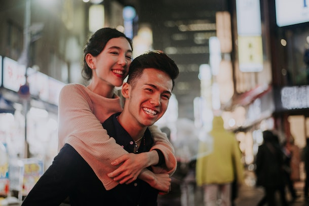 A woman laughs while on her boyfriend's back in the middle of a busy city at night.