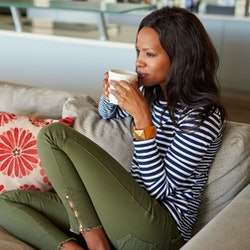 Attractive young woman drinking a cup of coffee while relaxing on a sofa at home
