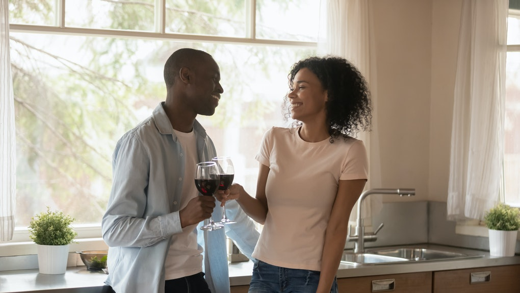 African couple in love standing in kitchen distracted from preparing dinner, diverse 30s spouses happy wife and husband clinking glasses with wine talking enjoy romantic dating at home concept image