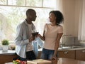 African couple in love standing in kitchen distracted from preparing dinner, diverse 30s spouses hap...