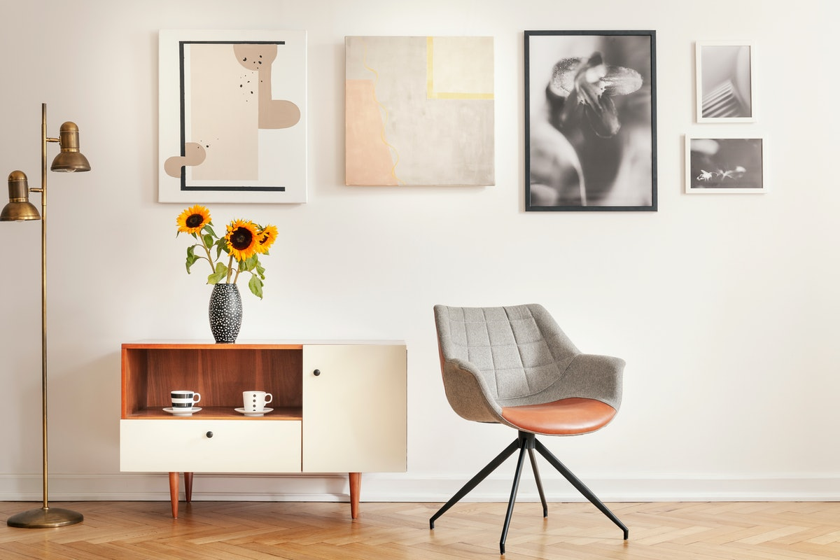 Grey armchair next to cupboard with sunflowers in white room interior with gallery. Real photo
