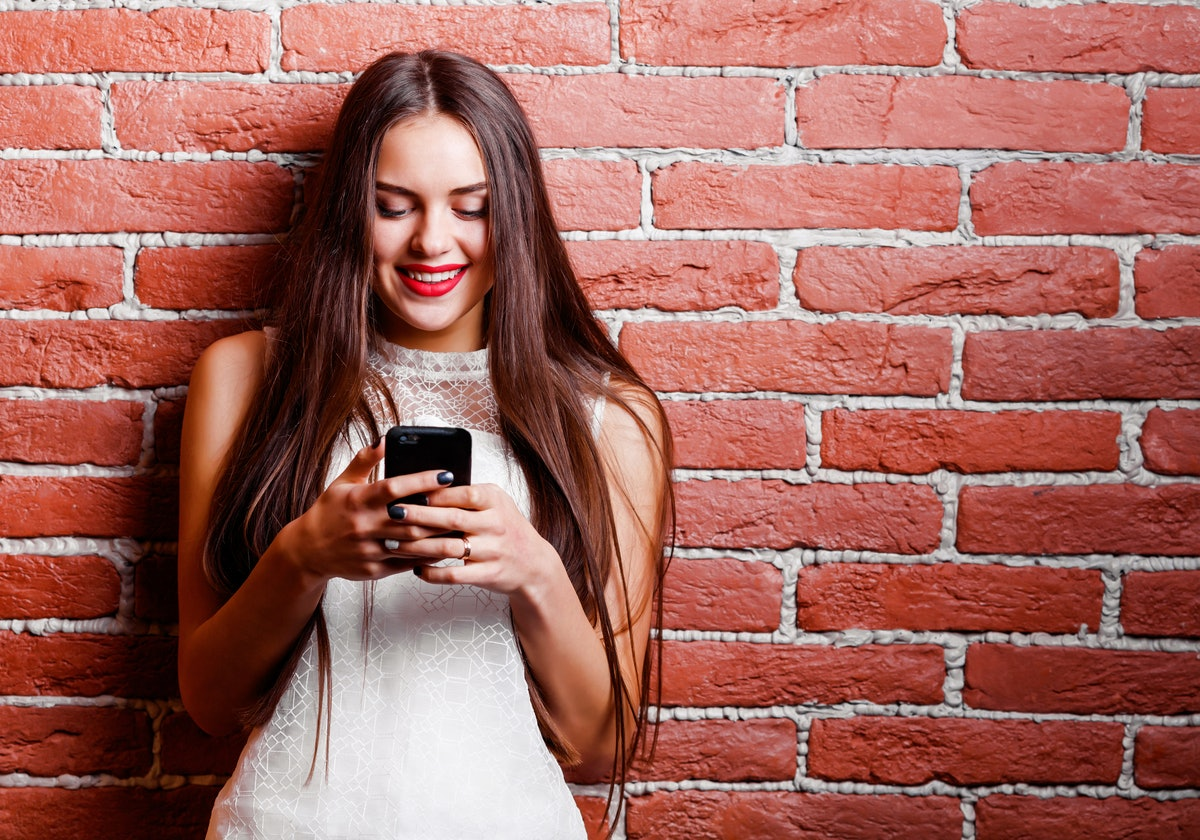Girl texting on phone on brick wall