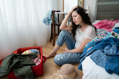 Young unhappy asian woman with suitcase sits on wooden floor in bedroom. worried female hand putting...