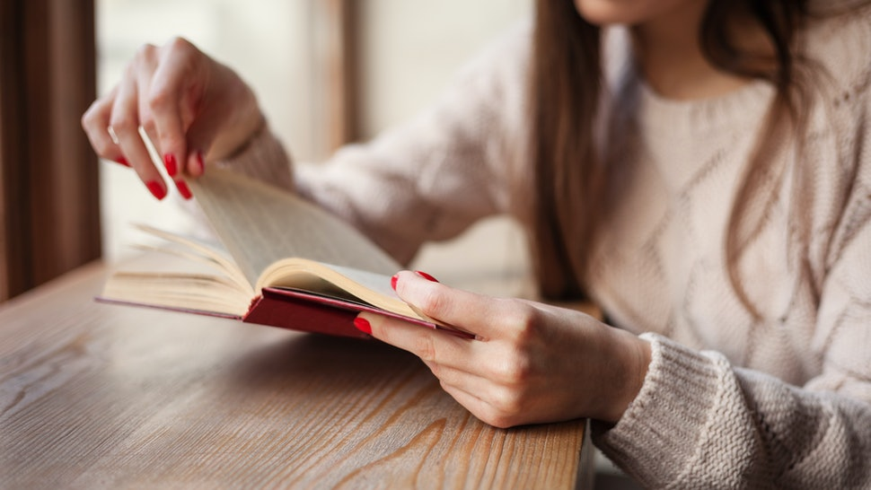 Girl holding a book wearing in warm wool pullover with red gel polish manicure. Wood retro background. Student woman concept.