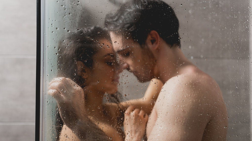 selective focus of sexy man and beautiful woman hugging in shower cabin