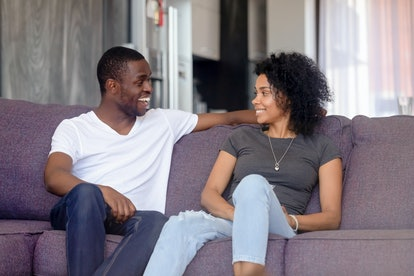 Black couple or just friends sitting on sofa in living room communicating talking at home spouses lo...