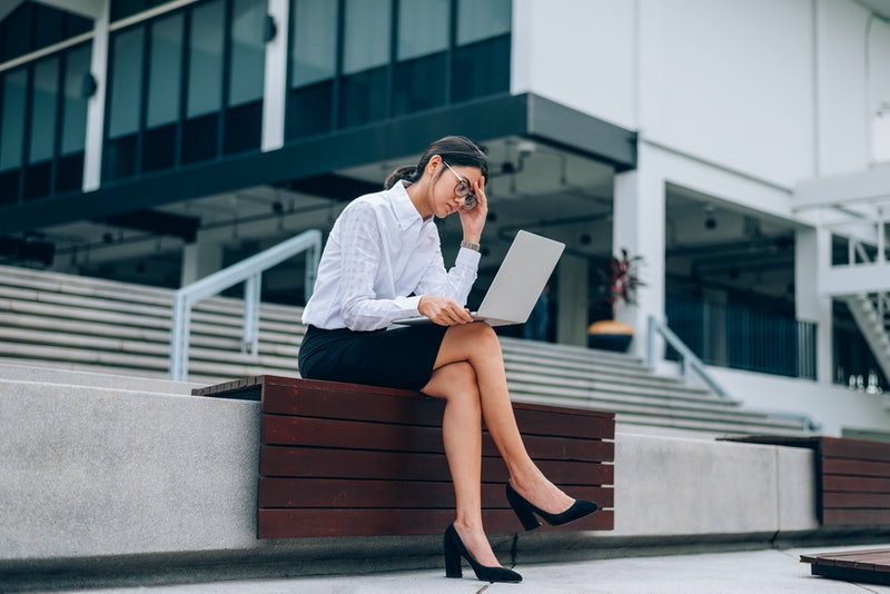 Asian businesswoman in eyeglasses using laptop working about business and finance feeling stressful- headache sitting in front office background- woman office worker and businesswoman concept