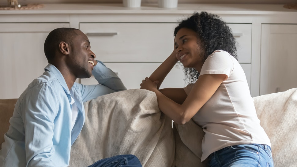 African couple sit resting on couch flirting enjoy romantic date, mixed race wife black husband having heart-to-heart talk spend time together, heterosexual friends or neighbors warm relations concept