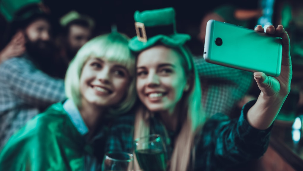 Two happy friends take a selfie at a bar on St. Patrick's Day.